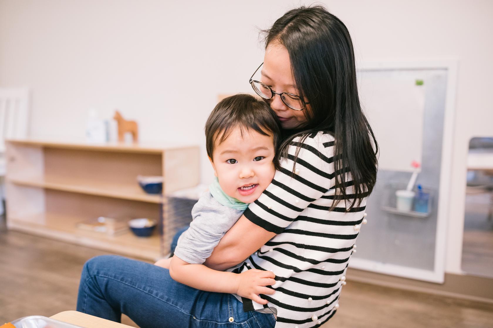 Nurturing guide at Guidepost Montessori hugs child