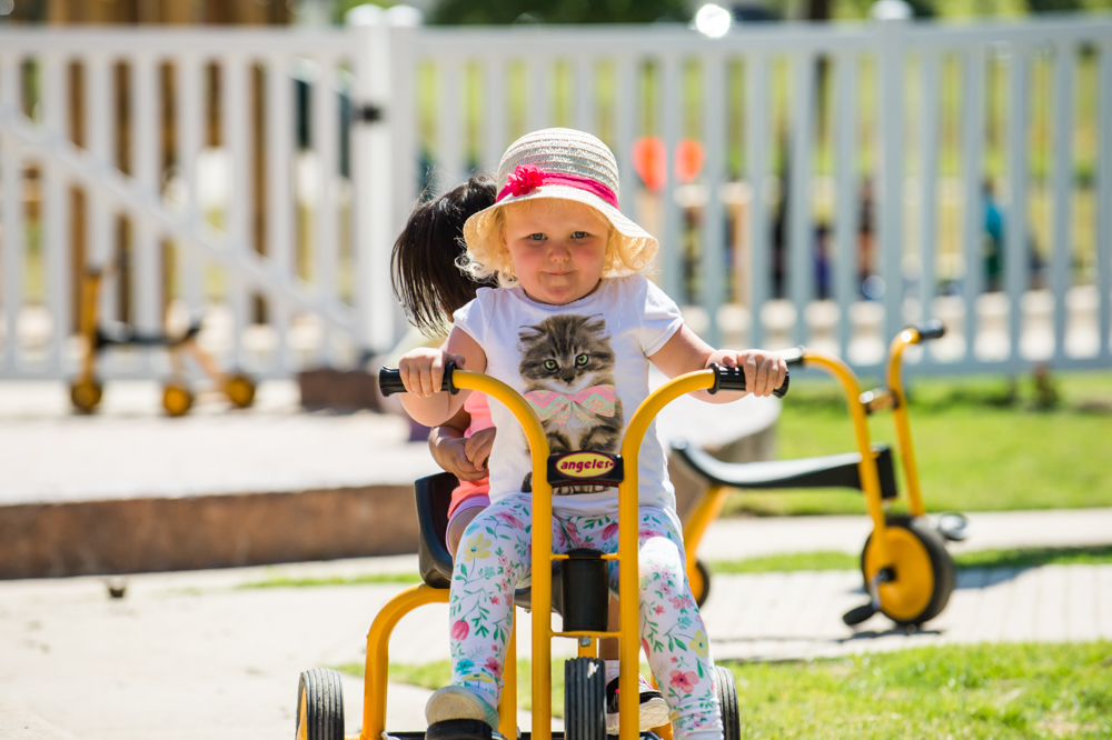 child riding tricycle at Guidepost Montessori