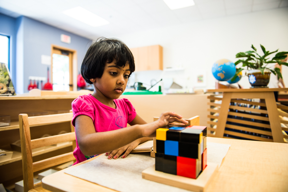 kindergarten student learn math by working with trinomial cube in a Guidepost Montessori classroom