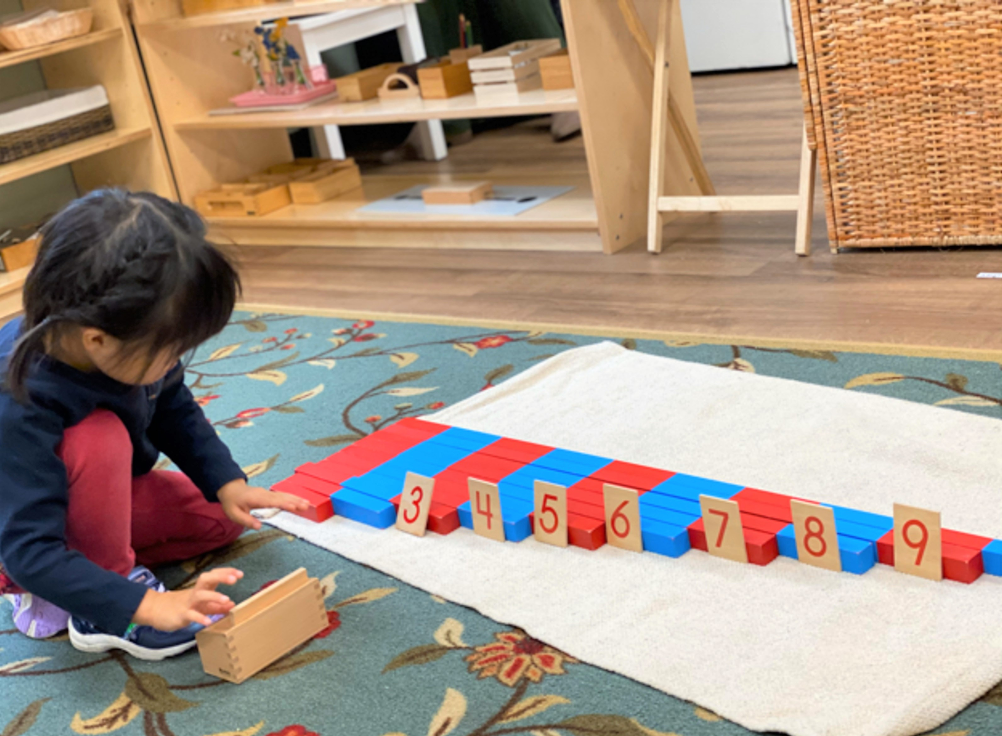 young child learns to count to 10 with the Montessori number rods at Guidepost Montessori
