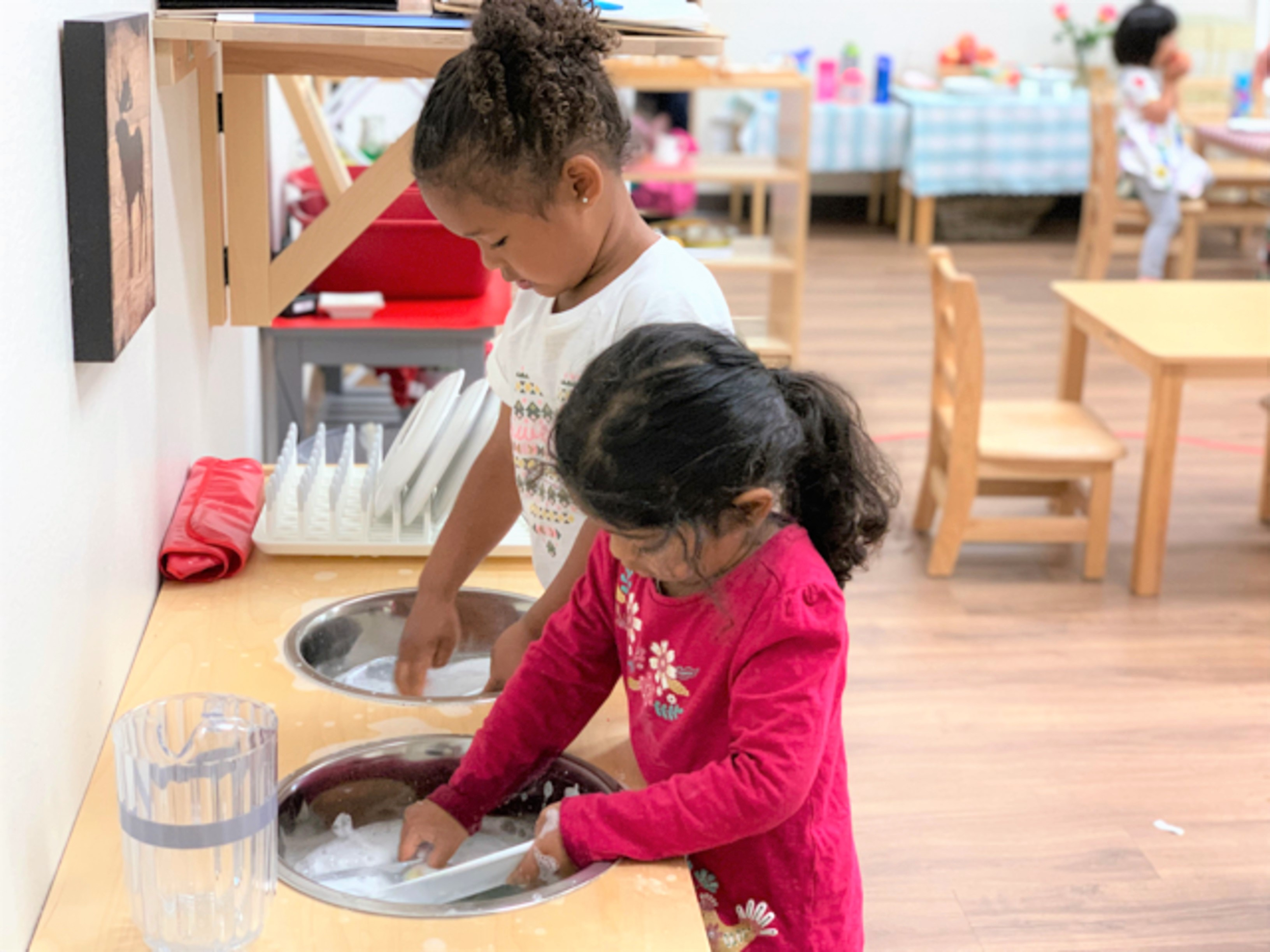 diversity and mixed age groups in a Montessori class allow an older child and younger child to learn from each other while washing dishes