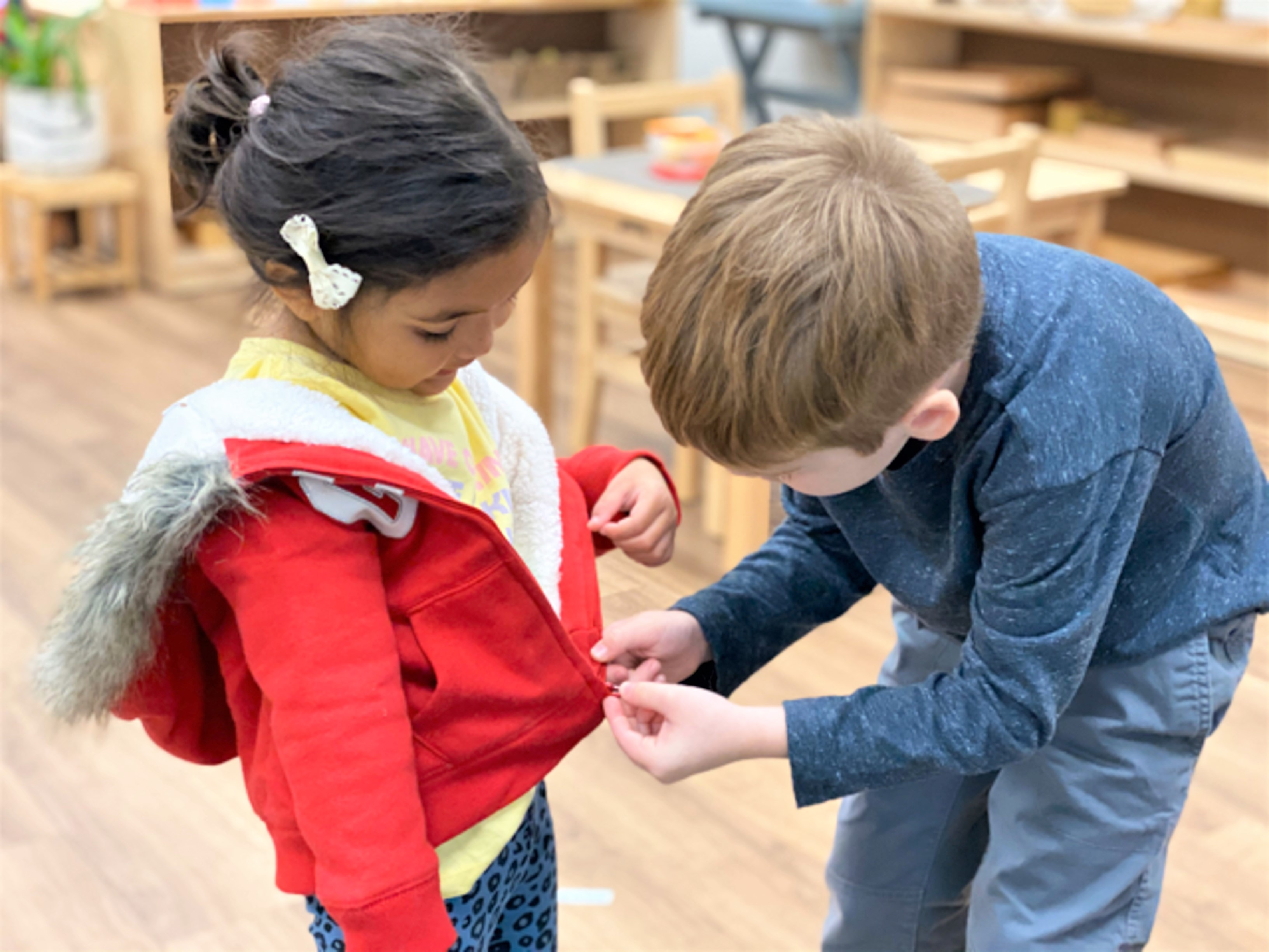 in a diverse and mixed-age classroom, an older boy helps a younger girl zip her jacket