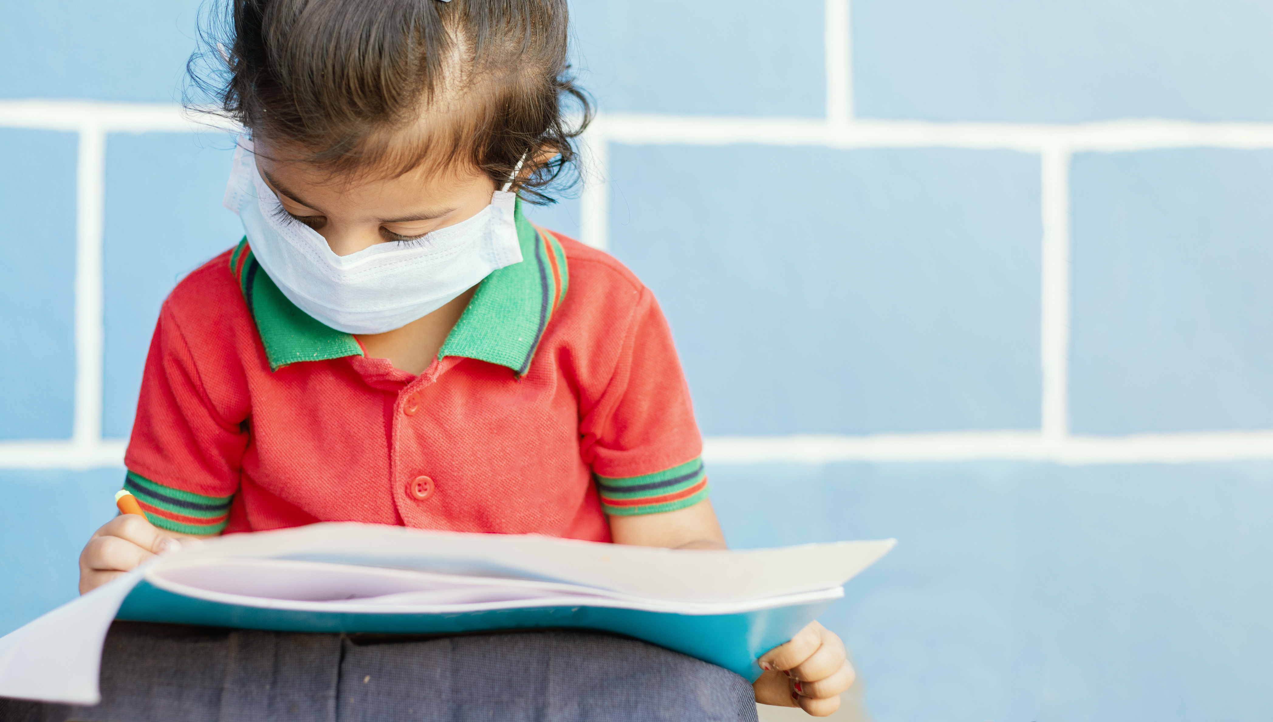 child writes in a notebook while wearing a face mask