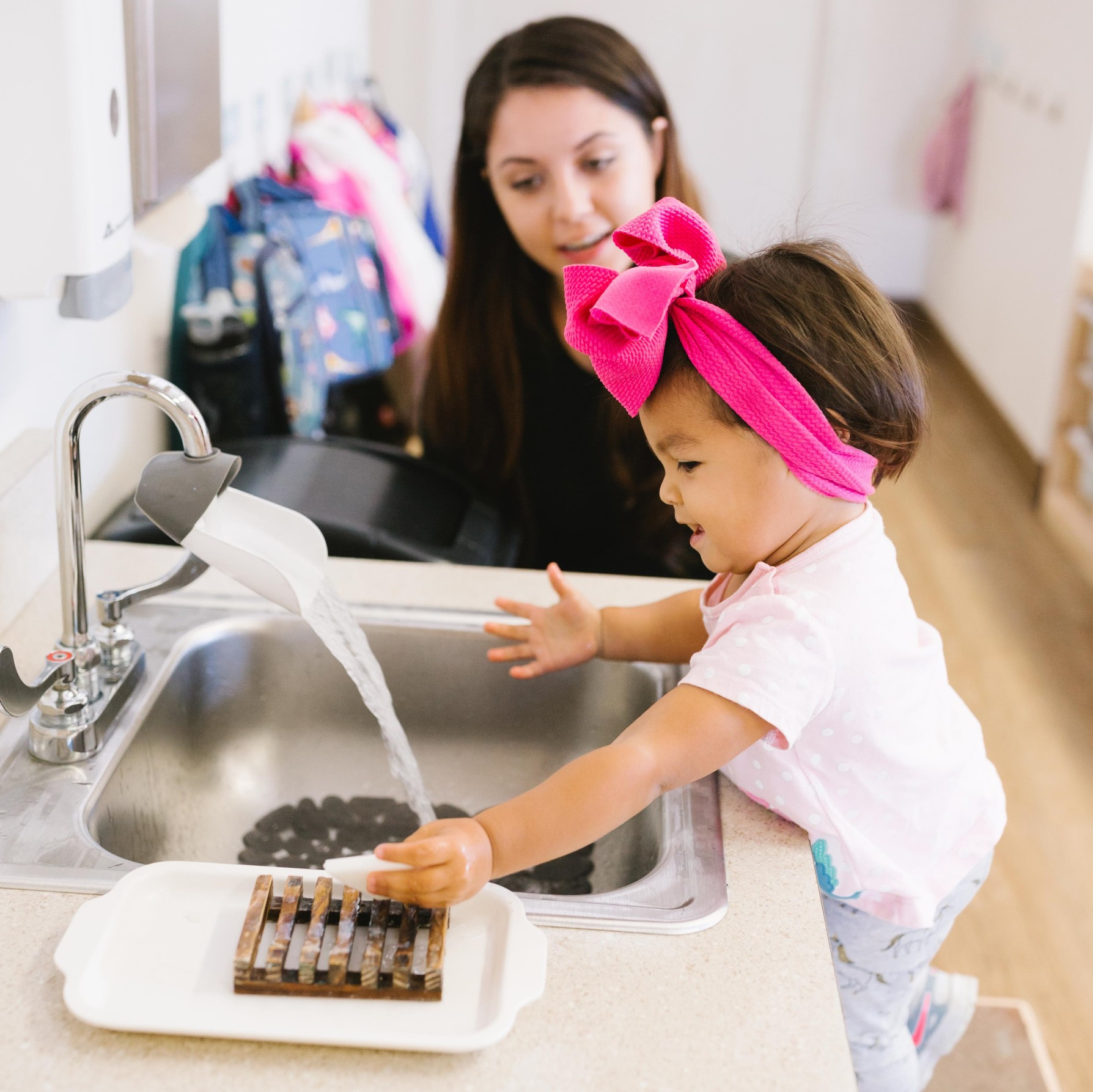 child washes her hands at Guidepost Montessori